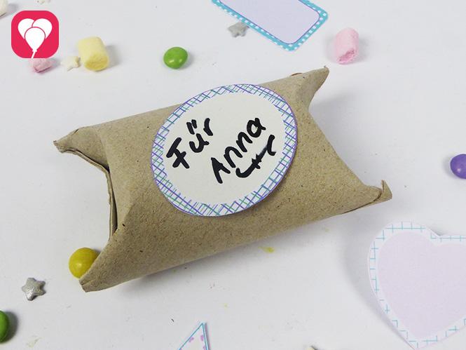 Geschenkverpackung aus Klopapierrollen dekoriert mit suessen Stickern