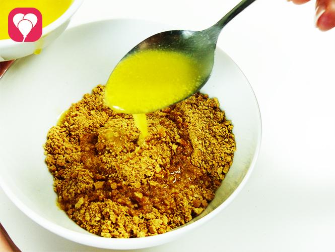 Käsekuchen backen - Kekskrümel mit zerflossener Butter vermischen